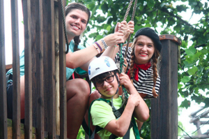 3 kids on a rope smiling for camera